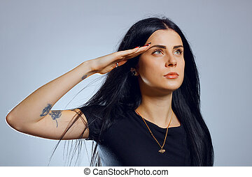 Salute - Attractive young gothic girl saluting over grey...