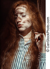 Tender red haired woman with freckles. Woman with shadow on her face