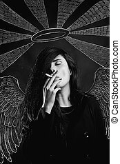 Fallen angel - Seductive young girl with angel wings smoking...