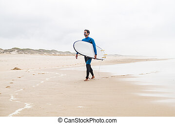 Young male surfer wearing wetsuit, holding surfboard under...