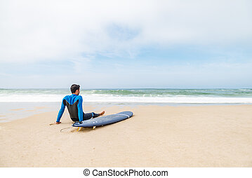 Young male surfer wearing wetsuit, sitting beside his...