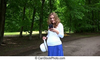 Smiling cute pregnant woman with hat and phone in her hands...