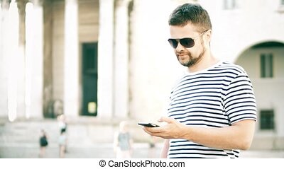 Young handsome man using his smart phone on the street