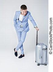 young man in blue suit with suitcase - Handsome elegant...