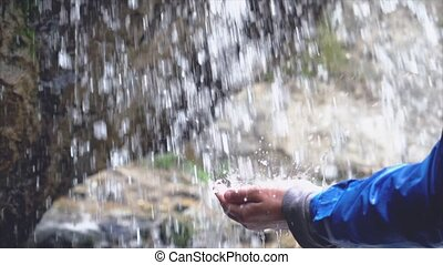 Young man refreshing his face and drinking water in stream of waterfall in Slow Motion.