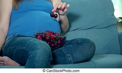 Pregnant woman hands stroke big belly and bowl with cherry...