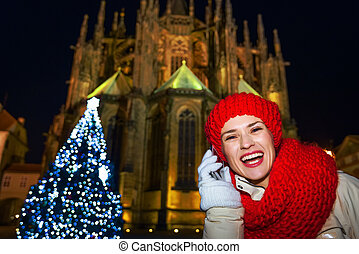 smiling tourist woman in Christmas Prague speaking on smartphone