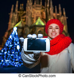 woman in Christmas Prague showing smartphone blank screen