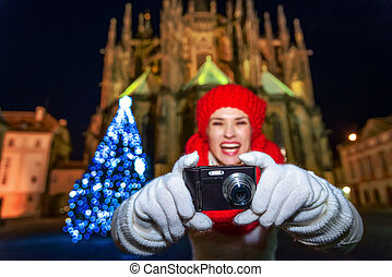 woman in Christmas Prague taking photo with digital camera