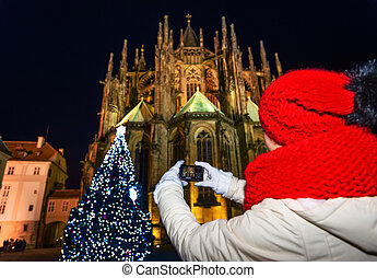 woman in Christmas Prague with digital camera taking selfie