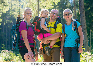 Family with two daughters on hike in the woods backlit in...
