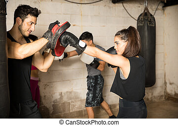 Using boxing mitts during boxing class - Group of people...
