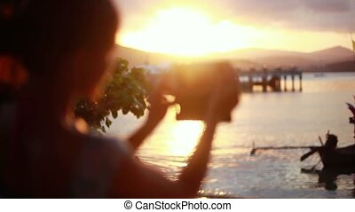Blurred woman taking photo of the sunset with her phone on...