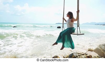 Dreamy young woman wearing sunglasses relaxes on the swing...