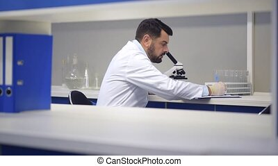Mature scientist looking through microscope and noting...