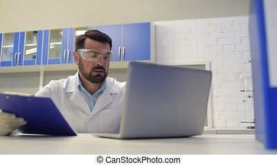Concentrated scientist working with documents and typing -...