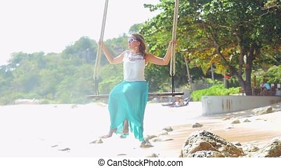 Pretty young woman relaxes on the swing at the stones beach...