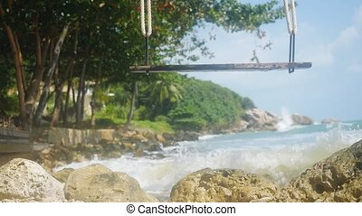 Tropical Island beach with swing. Splashing waves in the Sea...
