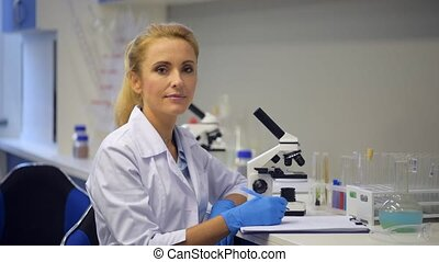Female scientist posing for camera while working in...