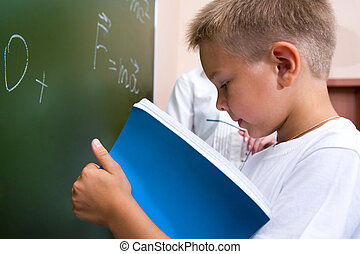 Homework - Photo of elementary student holding copybook and...