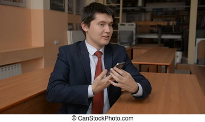 Portrait of a young businessman talking on a cell phone. A...