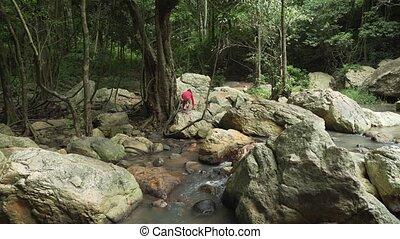 Young girl walks the rocks at Na Muang Waterfall on Koh...