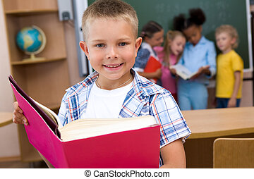 Reading lesson - Image of smart schoolboy with open book in...