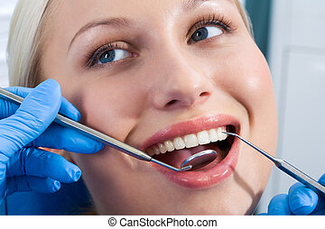 Dental checkup - Close-up of young woman during inspection...