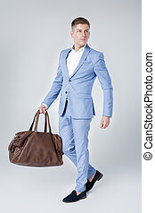 young man in blue suit holding leather bag - Handsome...