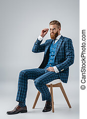 handsome man in blue suit sitting on chair isolated on grey
