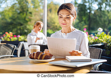 Beautiful woman working with documents in a cafe - Not...