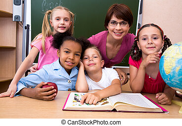 In the classroom - Portrait of teacher and children looking...