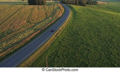 aerial view of sport car driving in fields at evening
