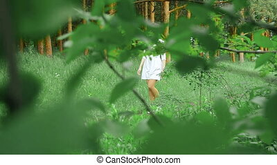 latin girl in white dress walks on a footpath in a forest -...