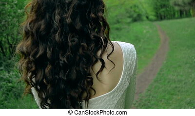 brunette with curly hair in white dress walks on a footpath...