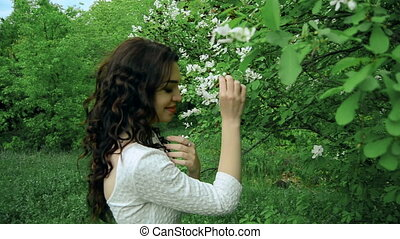 pretty brunette with curly hair smells a flowers in a park...