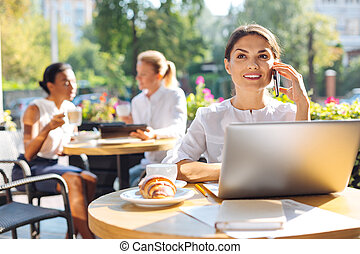 Cheerful woman making a call while sitting on restaurant...