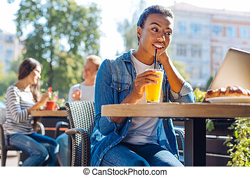 Cheerful woman sipping juice while watching TV-show in cafe...
