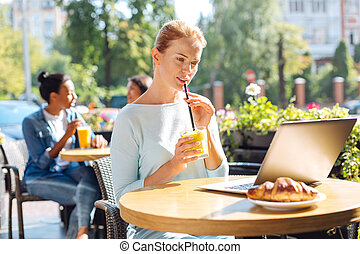 Young woman drinking smoothie and watching video on laptop -...