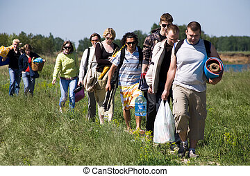 Go hiking - Image of queue of tourists walking down green...
