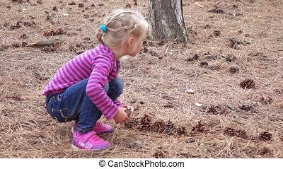 Baby girl collects pine cones - Girl child in the forest...