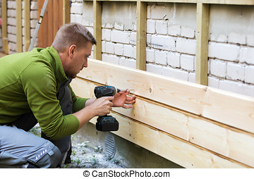 construction worker installing new wooden planks on old house brick facade