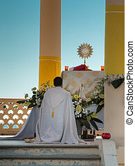 Priest Kneel Down in front of an Altar: Outdoor Church -...