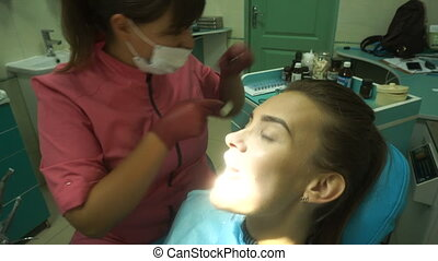 attractive young girl treats her teeth from a dentist