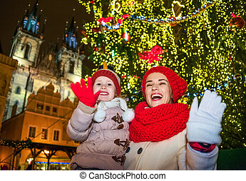 mother and daughter travellers in Christmas Prague handwaving