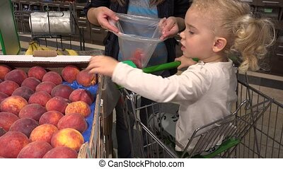 cute little girl in shopping car help mother to pick peach...