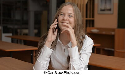Portrait of cheerful young woman talking on cell phone....