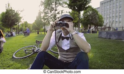 Mature businessman with camera and bicycle in the city park....