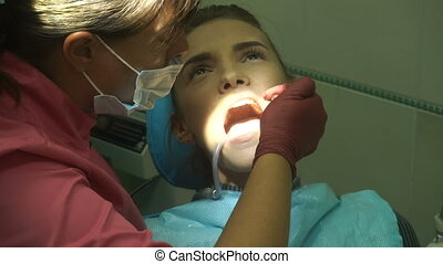 young girl treats her teeth from a dentist