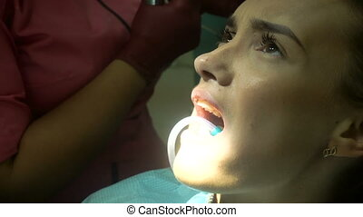 young cute woman treats her teeth from a dentist